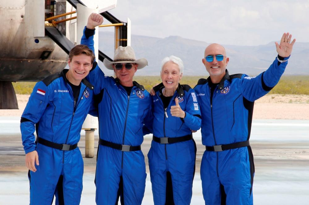 จากซ้ายไปขวา : โอลิเวอร์ แดเมน, เจฟฟ์ เบซอส,วอลลีย์ ฟังก์ อดีตนักบินอวกาศหญิงรุ่นบุกเบิก วัย 82 ปี และ มาร์ก เบซอส น้องชายของเจฟฟ์ เบซอส