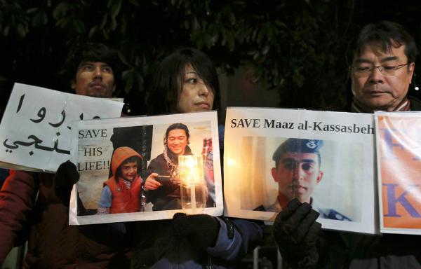 ชาวญี่ปุ่นออกมาชุมนุมเรียกร้องให้รัฐบาลช่วยเหลือนายเคนจิ โกโตะ และนายมูอัซ อัล-คาซาสเบห์ (ภาพ AP Photo)