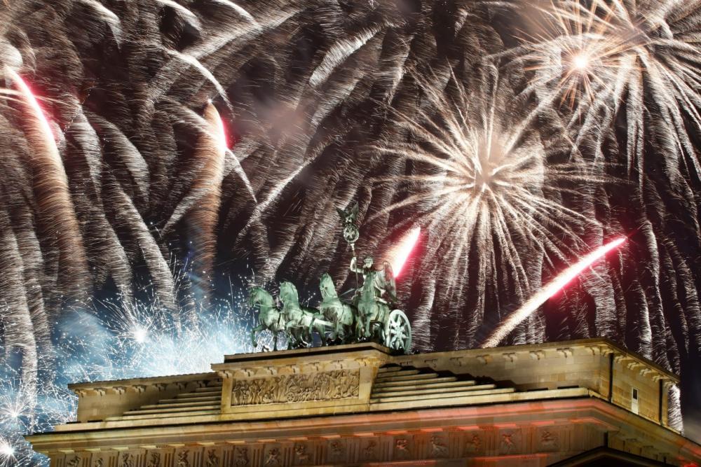 ดอกไม้ไฟระเบิดเหนือรูปปั้นรถศึกเทียมม้า 4 ตัว บนประตูบรานเดนบวร์ก ในกรุงเบอร์ลิน